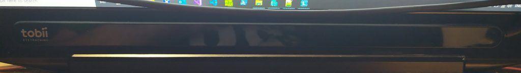 La imagen muestra el Tobii Eye Tracker 4C montado en la parte inferior de la pantalla para controlar el ordenador con los ojos