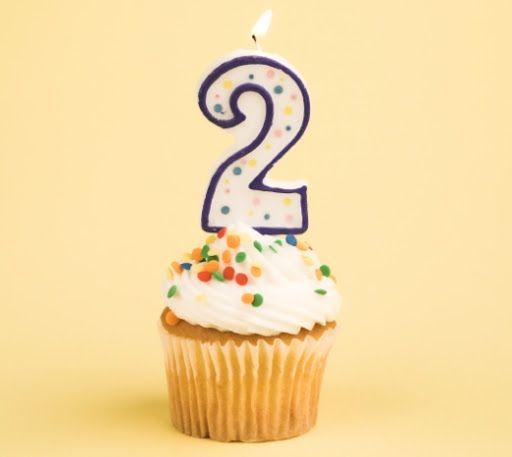 Imagen ornamental. Pastel de cumpleaños con una vela en forma de número 2